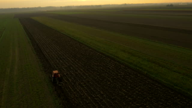 AERIAL Farmer Plowing The Field At Dusk