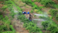 Farmer  spraying pesticide or fertilizer in field