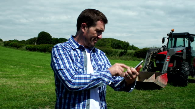 Landwirt verwenden digitale Tablet mit Traktor (Farm Landwirtschaft)