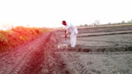 Farmer working in the field using hoe during sunset