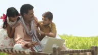 Farmer working on a laptop with his children playing with him