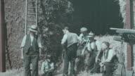 1938 MONTAGE Farmers near a barn having tea on their midday break / United Kingdom