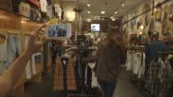 fashion blog filming girl walk through vintage clothing store