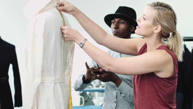 Fashion designer at work in studio training apprentice