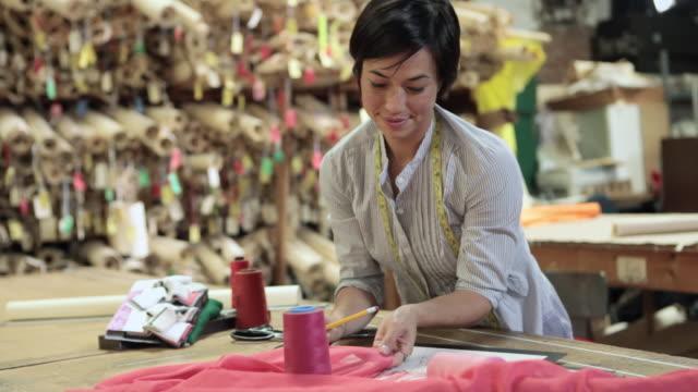 Fashion designer working and smiling at camera