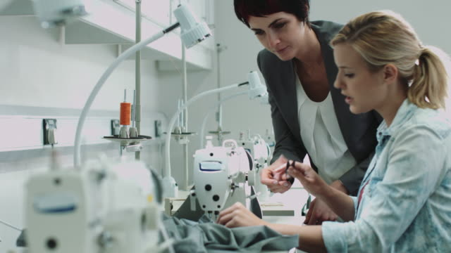 Fashion designers at sewing machine working together
