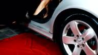 Weiblichen Fotomodell heraustreten aus dem Auto
