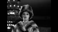 / fashion show in the Excelsior Hotel in Rome / women in fur coats and hats walk down a small runway with crowd on either side / CU model's...