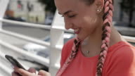 Fashionable girl surfing in smartphone while sitting outdoors