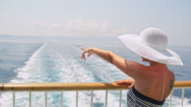 Fashionable woman pointing on island while cruising