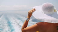 Fashionable woman with white sun hat on the ferry
