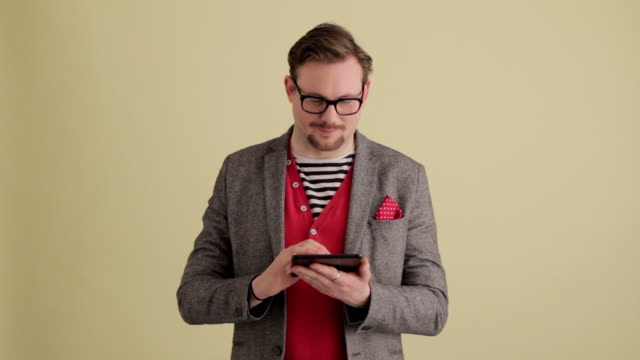 MWS fashionable young man using mini  tablet looking and smiling at camera