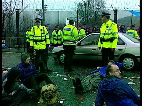 Faslane Nuclear Submarine Base EXT MS AntiNuclear protestors linking arms outside base as held back by police TGV Demonstrators staging sit down...