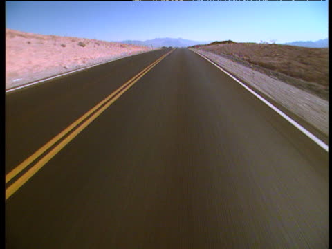 Fast forward track along empty highway surrounded by barren landscape Las Vegas