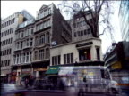 Fast motion of traffic passing by shops in central London