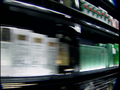 Fast tracks past shelves of perfumery stacked with bottles of fragrance