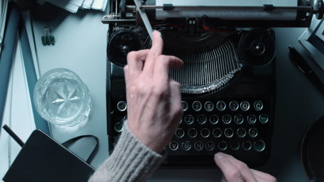 DS Fast typing on old typewriter behind stacked office desk