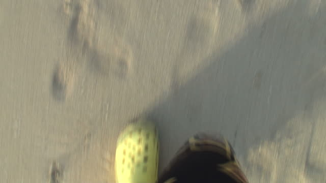 Fast walking along the beach; close-up on feet
