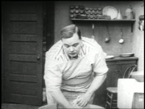 B/W 1915 fat man (Fatty Arbuckle) washing clothing with washboard + looking at something offscreen