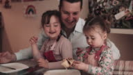 Father and children eating pancakes at home