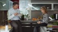 MS Father and daughter (10-11) eating cornflakes in kitchen / Kleinmachnow, Brandenburg, Germany