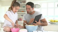 Father And Daughter Following Cake Recipe On Digital Tablet