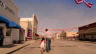 Father and daughter holding hands and walking up street after parade / American flag banners strung across street / California