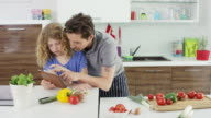 father and daughter in kitchen with tablet-computer