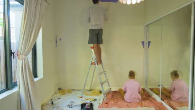 MS T/L TU TD ZI Father and daughter moving furniture and painting wall with purple color at bedroom / Melbourne, Victoria, Australia