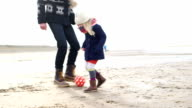 MS TS Father and daughter playing football on beach