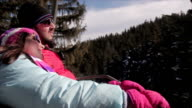 Father and daughter rides on ski lift