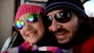 Father and daughter rides on ski lift,close up