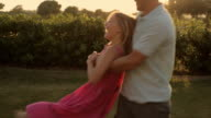 father and daughter twirling in sunset