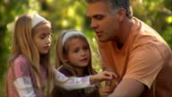 Father and daughters looking at leaves