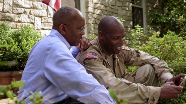 Father and military son watching cell phone on front stoop