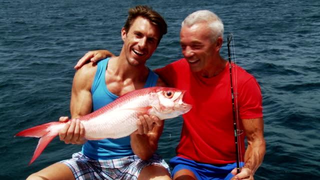 Vater und Sohn Genießen Sie Ihren Fisch
