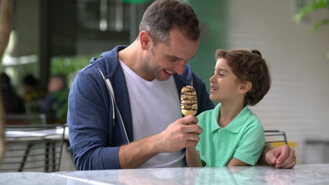 Father and son at the ice cream parlor sharing an ice cream looking happy