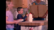 A father and son carry in the groceries, while the girls help their mother put dishes away in a cupboard.
