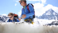 Father and son check GPS for directions while ascending mountain