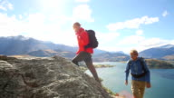 Father and son climb rock bluff above lake and mountains