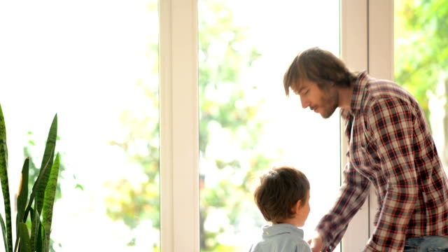 DOLLY: Father and son embracing in front of window