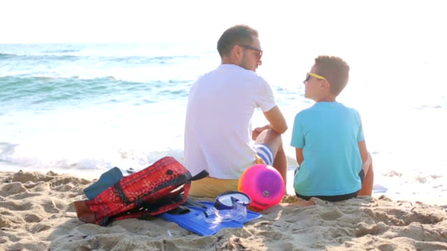 Father and son enjoy in sunrise on the sand