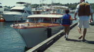 WS Father and son (8-9) getting on boat with fishing gear / Seattle, Washington, USA