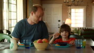 CU, Father and son (6-7) having breakfast in cottage, North Truro, Massachusetts, USA