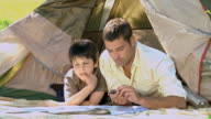 MS Father and son looking at map near tent in Park / Cape Town, Western Cape, South Africa