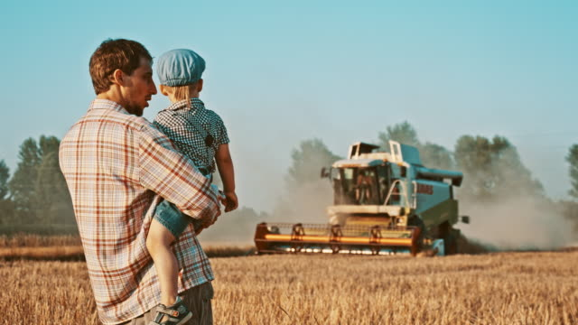Father and son looking at the combine harvester in field