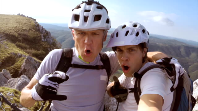 Father and son making funny selfies on top of mountain