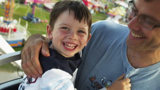 CU TS Father and son (2-3) on amusement park ride / Rutland, Vermont, USA