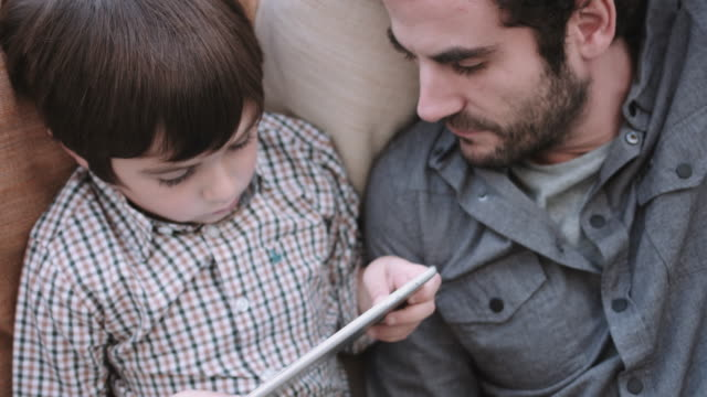 Father and son on the couch working on digital tablet and smart phone