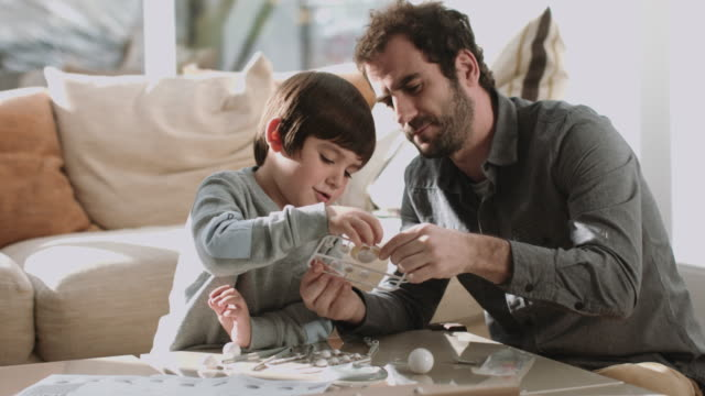 Father and son playing and painting